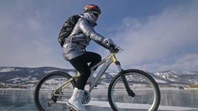 Frau fährt Fahrrad auf das Eis Das Mädchen wird in einer silbrigen unten Jacke, in einem Radfahrenrucksack und in einem Sturzhelm stock footage