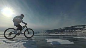 Frau fährt Fahrrad auf das Eis Das Mädchen wird in einer silbrigen unten Jacke, in einem Radfahrenrucksack und in einem Sturzhelm stock video