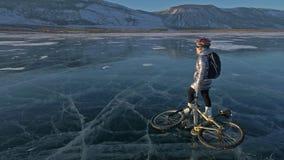 Frau fährt Fahrrad auf das Eis Das Mädchen wird in einer silbrigen unten Jacke, in einem Rucksack und in einem Sturzhelm gekleide stock footage
