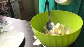 Frau fügen Butter und Zucker Nahrung hinzu Kochen eines Kuchens der Kekskrumen und des Milchgelees Auf der Oberfläche der Tabelle stock video