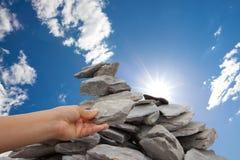 Frau fügt Felsen Steinhaufen unter Sonne gefülltem Himmel hinzu stockfoto