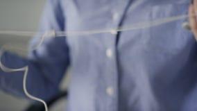 Frau fügt weiße Kopfhörer in Handy im Büro ein stock video footage