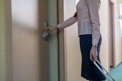 Frau öffnet Tür zum Raum unter Verwendung des elektronischen Schlüssels Stockbilder