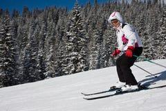 Frau fährt an einem Skiort Ski Stockfotografie