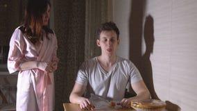 Frau fing einen Mann in der Küche nachts, als er Brötchen aß stock footage