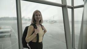 Frau am Flughafen, der das Flugzeug betrachtet stock footage