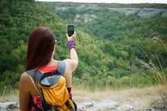 Frau fotografiert Berg unter Verwendung des Telefons Lizenzfreie Stockfotografie