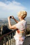 Frau fotografiert die schönen Umgebungen Lizenzfreie Stockfotografie