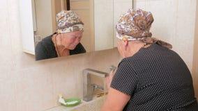 Frau gealterte Wäsche Ihr Gesicht mit Seife im Bad Es kann gesehen werden sich reflektierte in einem Spiegelkasten Spülungsseifen stock video footage