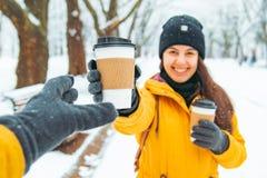 Frau geben dem Freund Tasse Kaffee Sitzung in geschneitem Winterpark stockbilder