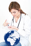 Frau geben Einspritzung zur Weltkugel auf Weiß Lizenzfreies Stockfoto