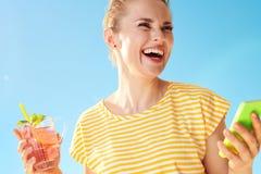 Frau gegen blauen Himmel mit Auffrischungscocktail und Smartphone Lizenzfreie Stockbilder