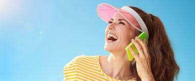 Frau gegen den blauen Himmel, der beiseite schaut und am Handy spricht Lizenzfreies Stockbild