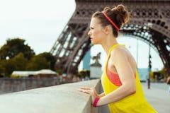 Frau gegen die klare Sicht des Eiffelturms untersuchend Abstand lizenzfreie stockfotografie