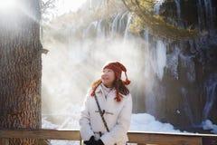 Frau gegen gefrorenen Wasserfall Stockbild