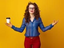 Frau gegen gelben Hintergrund mit Kaffeetasse in der Yogahaltung Stockfoto