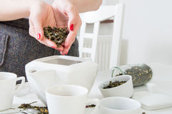 Frau gegossene grüne Teeblätter Lizenzfreie Stockbilder