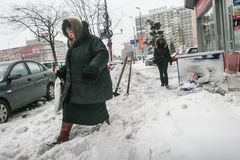 Frau geht auf die Straße, die im Schnee bedeckt wird Lizenzfreie Stockbilder