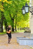 Frau geht an der Herbststadt Stockbild
