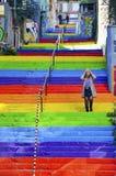 Frau geht in die Regenbogen-farbige Treppe Stockfoto