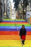 Frau geht in die Regenbogen-farbige Treppe Stockfotografie