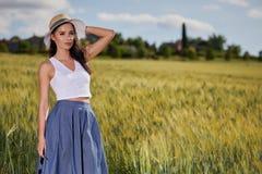 Frau geht entlang die Straße unter den Feldern Stockfotos