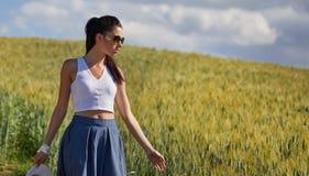 Frau geht entlang die Straße unter den Feldern Stockbild