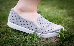 Frau geht in Gras, Schuh mit Punkten Stockfotos