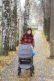 Frau geht in Herbstpark mit Buggy stockfotografie