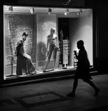 Frau geht hinter Shopfenster mit Mannequins Stockbild