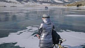 Frau geht neben Fahrrad auf dem Eis Das Mädchen wird in einer silbrigen unten Jacke, in einem Rucksack und in einem Sturzhelm gek stock video footage