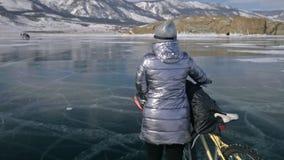 Frau geht neben Fahrrad auf dem Eis Das Mädchen wird in einer silbrigen unten Jacke, in einem Rucksack und in einem Sturzhelm gek stock video