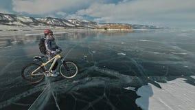 Frau geht neben Fahrrad auf dem Eis Das Mädchen wird in einer silbrigen unten Jacke, in einem Rucksack und in einem Sturzhelm gek stock footage