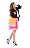 Frau geht und trägt Taschen mit Käufen Stockfotografie