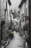 Frau geht vorbei in eine Straße des mittelalterlichen französischen Dorfs von Heilig-Guilhem-Le-Désert lizenzfreies stockbild