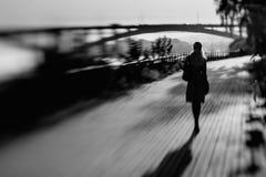 Frau geht zu einem Abstand auf der Straße Stockbild