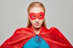 Frau gekleidet als Superheld mit dem Schauen ernst Lizenzfreie Stockfotos