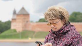 Frau gekleidet in der Sportjacke, die Handy hält stock video