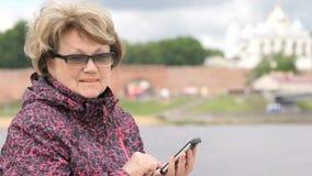 Frau gekleidet in der Sportjacke, die Handy hält stock footage