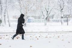 Frau gekleidet im schwarzen Mantel, der allein geht Lizenzfreie Stockfotografie