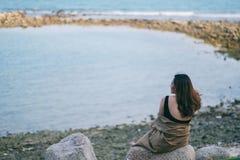 Frau genie?en, auf dem Felsen durch die K?ste zu sitzen stockfoto