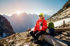 Frau genießen Berglandschaft und Trinkwasser, nachdem sie geklettert ist lizenzfreies stockfoto