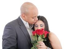 Frau genießt den Geruch, der von einem Blumenstrauß von Rosen gegeben wird. lizenzfreies stockbild