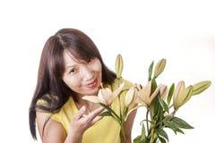 Frau genießt den Geruch von Lilien lizenzfreie stockbilder