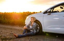 Frau geparkt am Straßenrand bei Sonnenuntergang Stockfotos