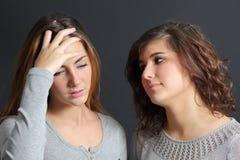 Frau gesorgt und eine andere sie tröstend Stockbild