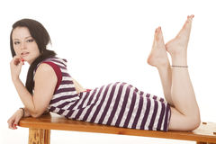 Frau gestreifter purpurroter Kleiderlagemagen lizenzfreies stockbild