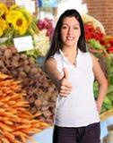 Frau gibt Daumen am Landwirt-Markt auf Lizenzfreie Stockbilder