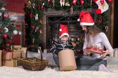 Frau gibt dem Sohn eingewickelte Weihnachtsgeschenkgeschenke stockfoto
