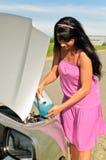 Frau gießt eine Flüssigkeit zum Auto Stockfotos